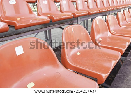 Red seats in a grandstand, detail of seats in a football field, spectators and sport - stock photo