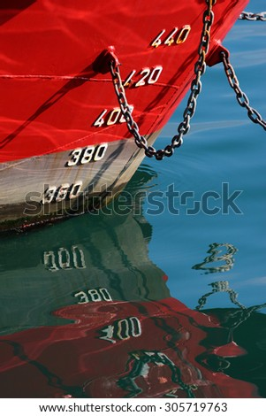 Red ship hull with waterline and draft scale measure - stock photo