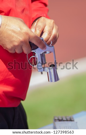 Red shirt man reloading ammo to silver gun - stock photo