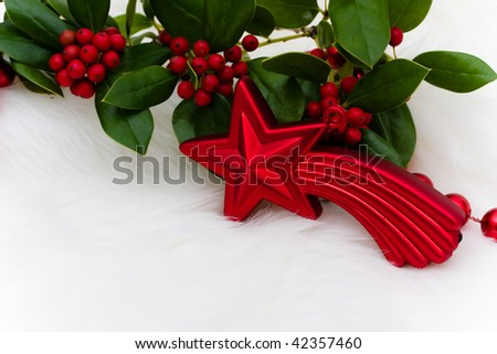 Red shooting star and holly and berries on a white fur background - stock photo