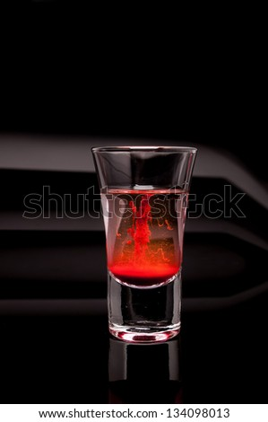 red shot glass on a dark background - stock photo