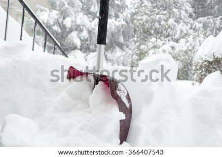 Red shovel close up in the snow on the porch. Deadly blizzard in Washington DC. Virginia  January 23 2015 - stock photo