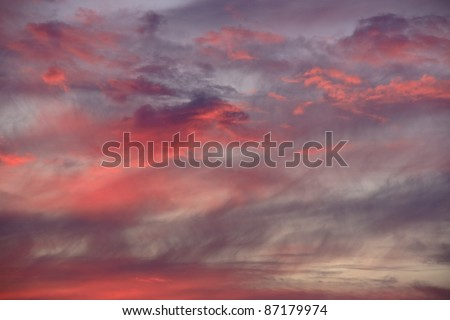 Red Sky at Night:  Clouds of brilliant reddish orange color accompanied by wispy strands of thin grey mixed in are caused by the setting sun - stock photo