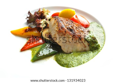 Red Snapper Steak with Green Sauce and salad - stock photo