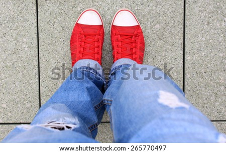 Red sneakers with fashion jeans, view from above - stock photo
