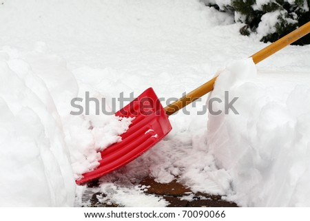 Red snow shovel scooping snow. - stock photo