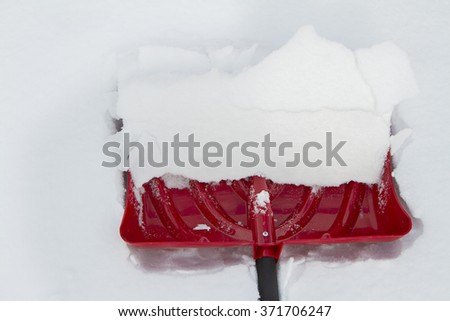 Red snow shovel with a scoop of snow in it on snow - stock photo
