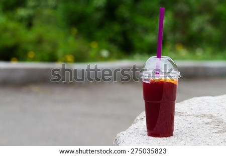Red soft drinks with slice of orange in takeaway cup - stock photo