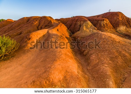 red soils around the freshwater lake formed in a former quarry for the extraction of bauxite in Italy - stock photo