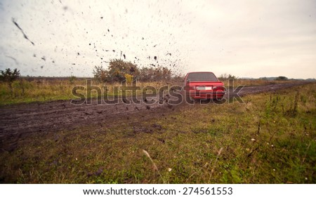 Red sport car drive on the dirt. - stock photo
