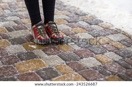 Red sport shoes are in winter park - stock photo