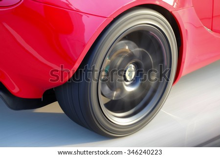 Red Sports car in Motion Wheel blur on a high speed road. - stock photo