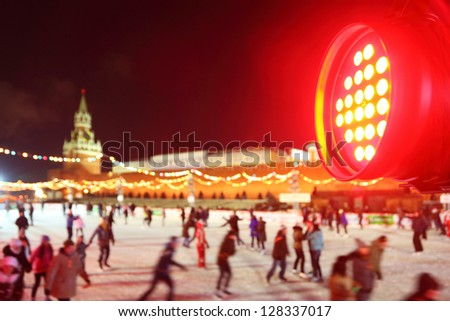 Red spotlight and people skate at GUM-Skating rink on Red Square in Moscow, Russia. Focus on spotlight. - stock photo