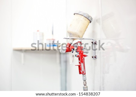 Red Spray Gun painting a car in special booth - stock photo