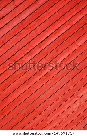 Red stained timber slats viewed diagonally to create abstract pattern background - stock photo
