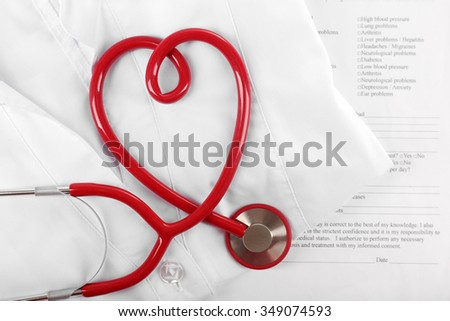 Red stethoscope, medical record and uniform, close up - stock photo