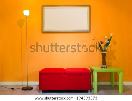 red stool chair, floor lamp, vase on green table and picture frame on orange wall - stock photo