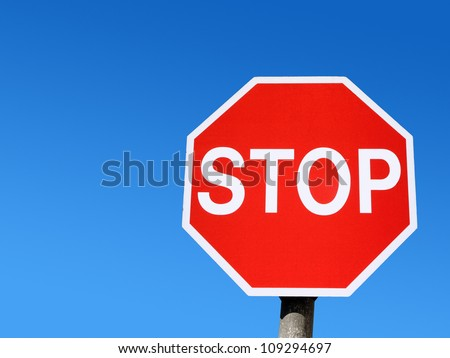 Red stop road sign and blue sky. - stock photo