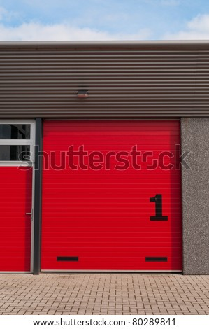red storage door os an industrial building - stock photo