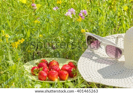 Red strawberries on a green plate, white hat, glasses on the background of green grass and wild flowers in the summer garden - stock photo