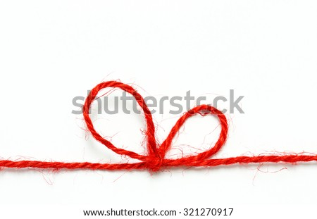 Red string bow on a white background. - stock photo