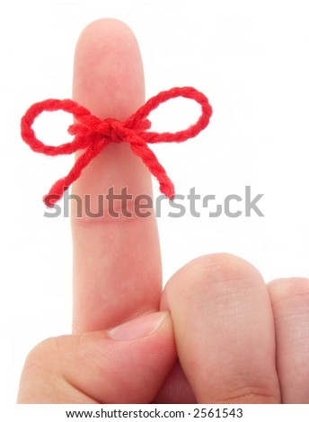 Red string tied around finger as a reminder, isolated on white background. - stock photo