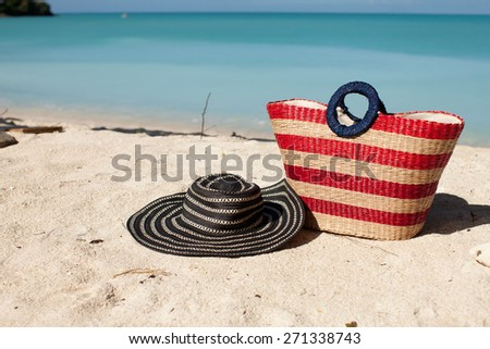 red striped bag and hat on the beach - stock photo