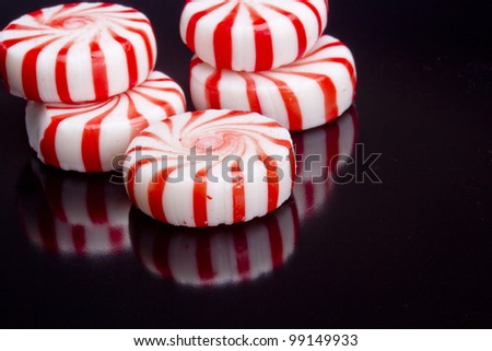 Red striped peppermints on a black background. - stock photo