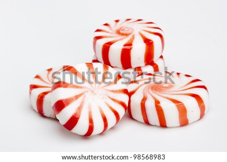 Red striped peppermints on a white background. - stock photo