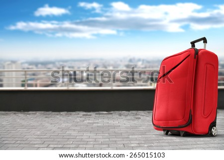 red suitcase gray pier and landscape of city  - stock photo