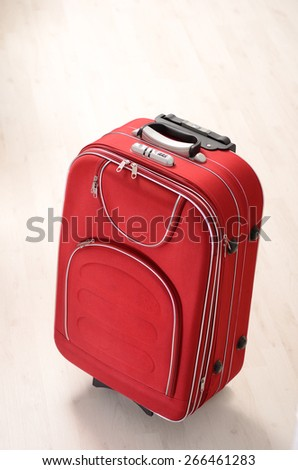 Red Suitcase on a wooden floor in empty room - stock photo