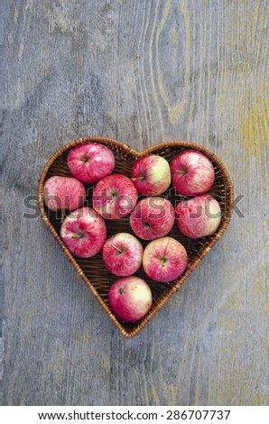 red summer fresh apple fruits in heart form wicker basket on table - stock photo