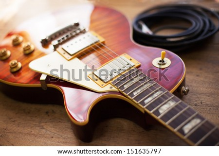 Red sunburst color single cutaway electric solid body guitar, and a reel of black instrument cable, on a old grungy wooden surface. Shallow depth of field.  - stock photo