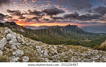 red sunrise with thunderclouds above the sea and mountains  - stock photo