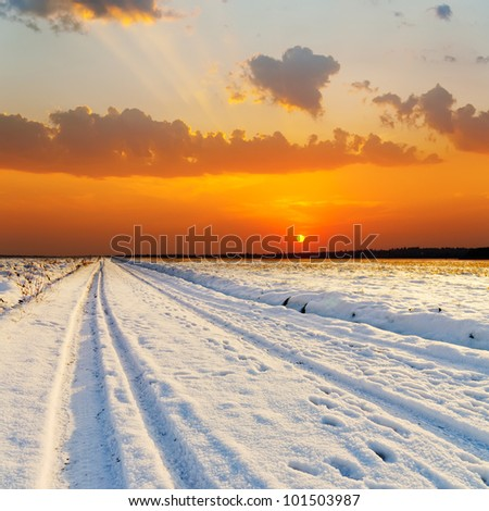 red sunset over road with snow - stock photo