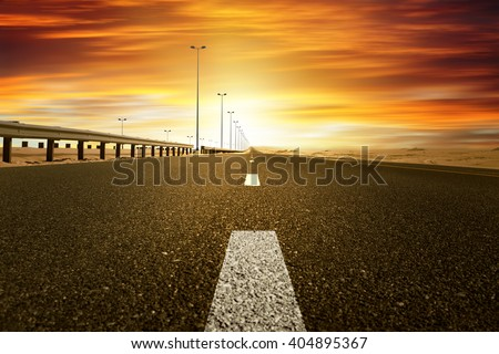 red sunset over the desert road in kuwait  - stock photo