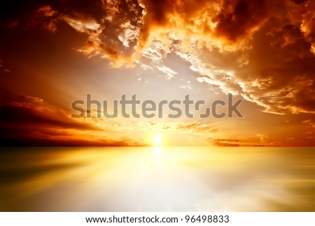 Red sunset over the sea, rich in dark clouds, rays of light - stock photo