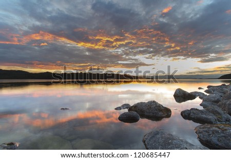red sunsets reflected in the clear water of the lake Kronotskoye, Kamchatka, Russia - stock photo