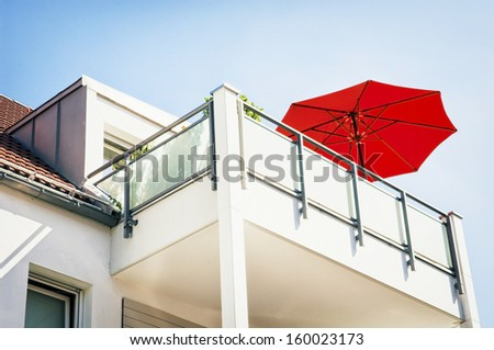 red sunshade at a modern balcony - stock photo