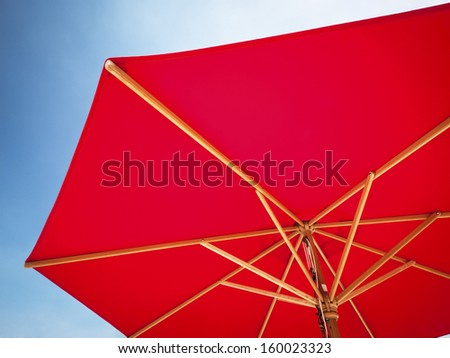 red sunshade in front of blue sky - stock photo