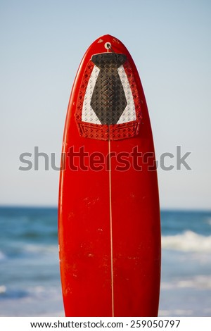 Red surfboard on the sand on a very beautiful sunny day - stock photo
