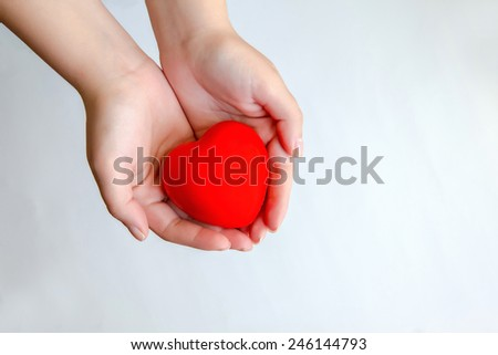 Red sweet heart in woman's hands - stock photo
