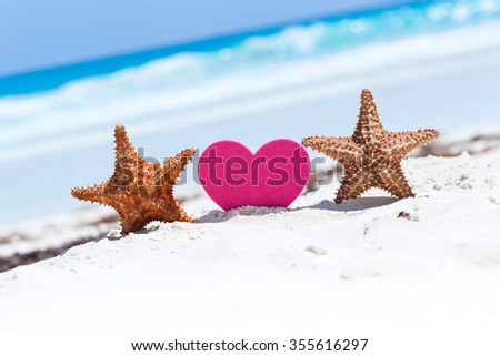 Red sweet heart shape with two starfishes on white sandy beach with sea background. Happy Valentines Day at summertime on exotic vacations. - stock photo