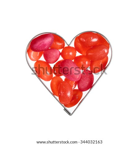 Red sweet jelly beans in heart shaped frame isolated over white - stock photo