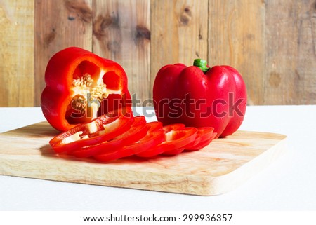 Red sweet pepper on a chopping board. - stock photo