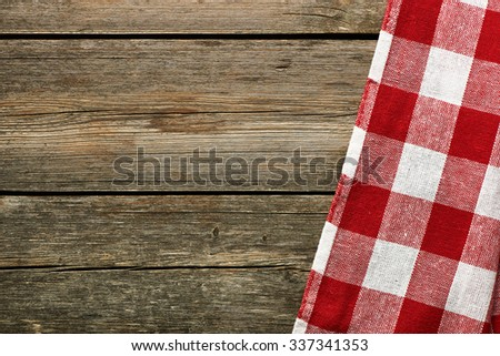 Red tablecloth on rustic background - stock photo