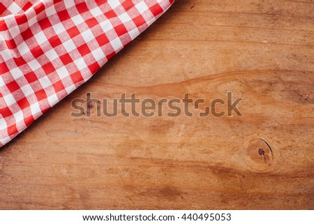 red tablecloth on wooden background - stock photo