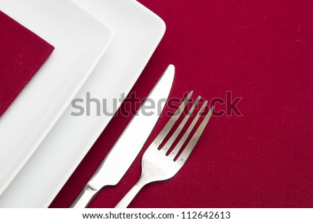 Red tablecloth with white square plates and red napkin - stock photo