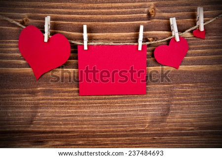 Red Tag Or Label With Three Hearts On A Line With Copy Space For Your Text Here On Wooden Background, Three Symbols, Vintage, Retro and Old Fashion Style With Frame - stock photo