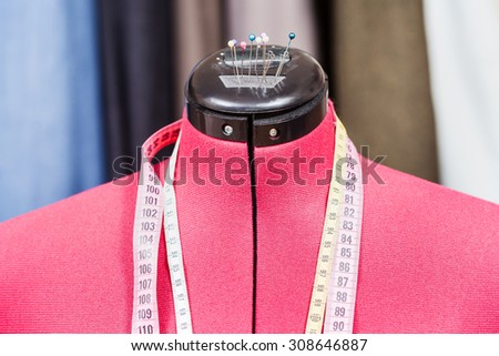 red tailor dummy - mannequin with measure tapes and clothes on background - stock photo